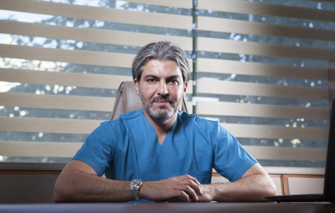 Dr Serkan Aygin sitting on the desk